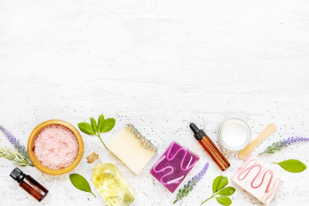 Top view of various colorful handmade organic soaps arranged with citrus fruits, herbs, chia seeds and aloe. white rustic background, copy space.