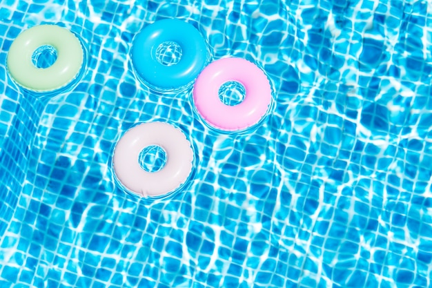 Top view of various colors floats in the pool summer concept illustration 3d