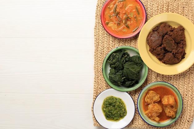 上面図マサカンパダンまたはパダン料理と呼ばれるパダンのさまざまな料理。インドネシアで人気の料理、西スマトラ州ミナン出身、白い背景のコピースペース