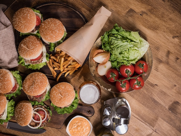 Top view of various fast food on a wooden table. beef meat. fresh tomates. great food.