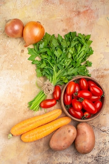 ローマトマト、ジャガイモ、タマネギ、ニンジン、コピースペースのある木製の背景に自家製サラダ用のパセリの束などのさまざまな新鮮な野菜の上面図