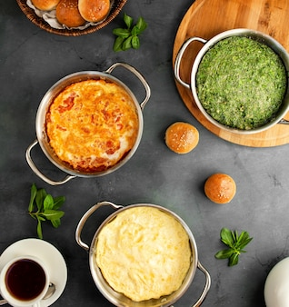 Vista superiore di varie uova di colazioni dell'uovo fritto con l'omelette classica dei pomodori e il kuku azero sul nero