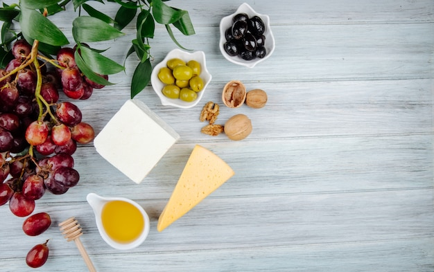Top view of various kind of cheese with fresh grape, walnuts, honey and pickled olives on grey wooden table with copy space