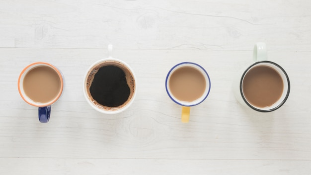 Top view of various kinds of coffee in cups arranged in a row over white wooden desk