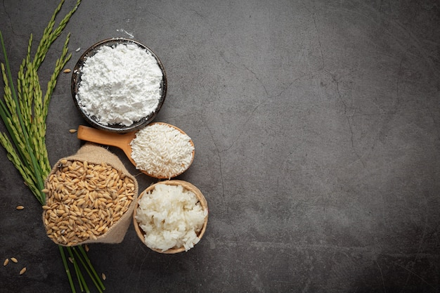 Top view of various kinds of produce from rice on dark floor