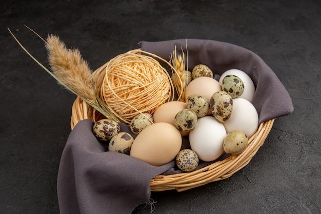 Vista dall'alto di varie uova organiche punta di corda su un asciugamano nero in un cesto su sfondo scuro