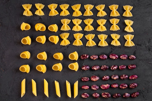 Top view of various raw pasta with kidney beans arranged on black