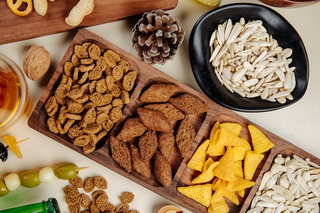 Top view of various salty beer snacks bread crackers corn cones  sunflowers seeds nuts and pickled olives on white