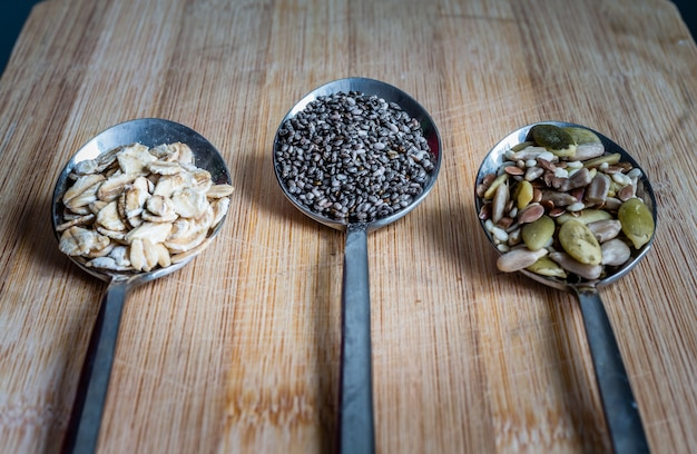 Top view, various seeds  in spoons on wooden table