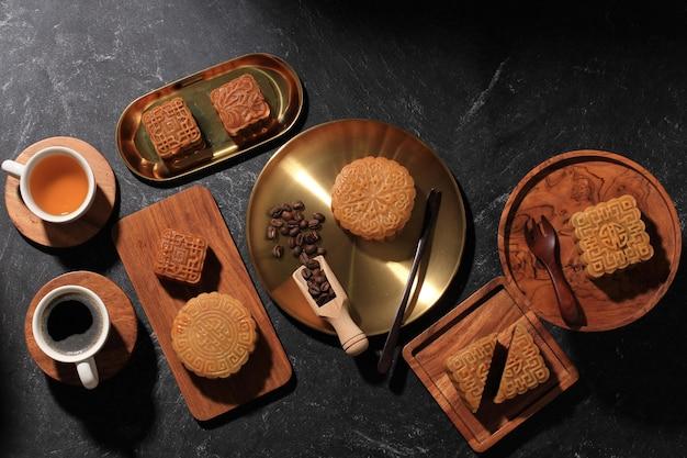 上面図さまざまな形の月餅(月餅)旧正月中秋節の中国のデザートスナック。コンセプトルスティカブラックアジアンベーカリー、紅茶とコーヒーを添えて。コピースペース