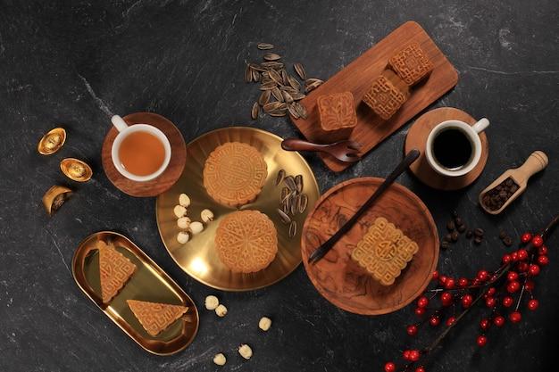 상위 뷰 다양한 모양의 월병(월병) 중국식 디저트 스낵은 음력 설 중추절 기간 동안입니다. 개념 rustica 블랙 아시아 베이커리, 차와 커피 제공. 복사 공간