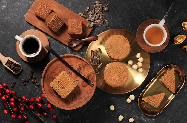Top view various shape moon cake (mooncake) chinese dessert snack during lunar new year mid autumn festival. concept rustica black asian bakery, served with tea and coffee. copy space