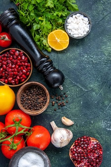 Вид сверху различные специи, мельница для перца, помидоры, чеснок, зелень, гранат на столе