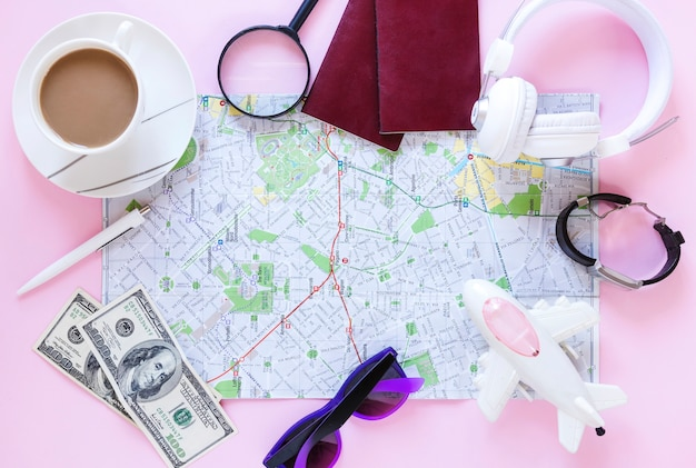 Top view of various traveler accessories and cup of tea on pink background