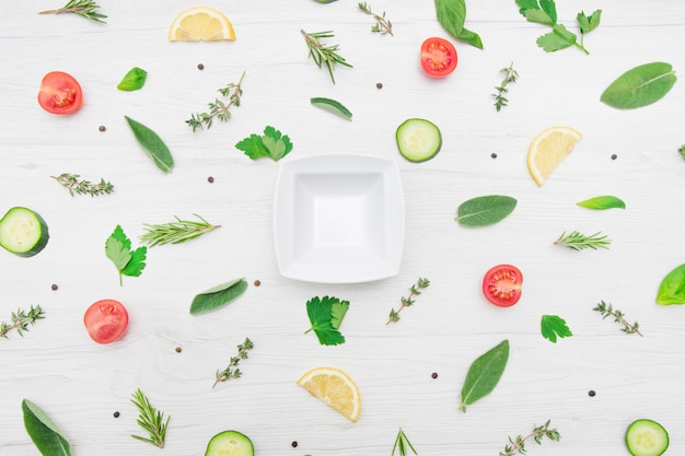 Top view of various types of aromatic herb leaves and cut vegetables on wooden background