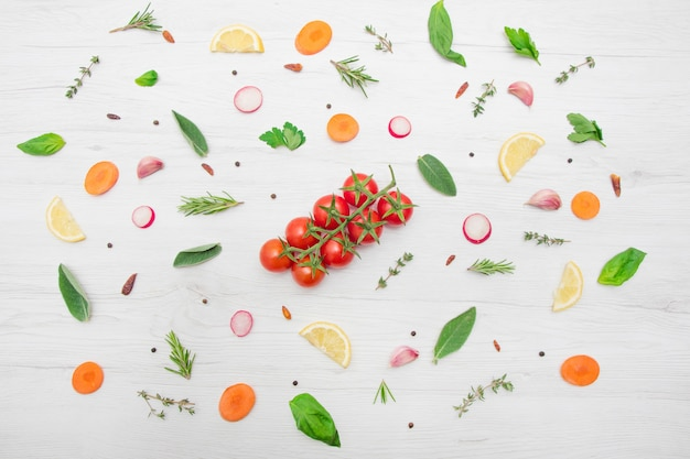 Top view of various types of aromatic herb leaves and cut vegetables