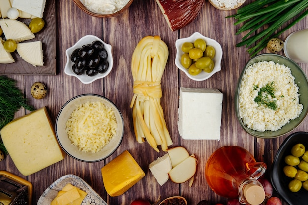 Top view of various types of cheese with green onio honey in a glass bottle and pickled olives on rustic wood