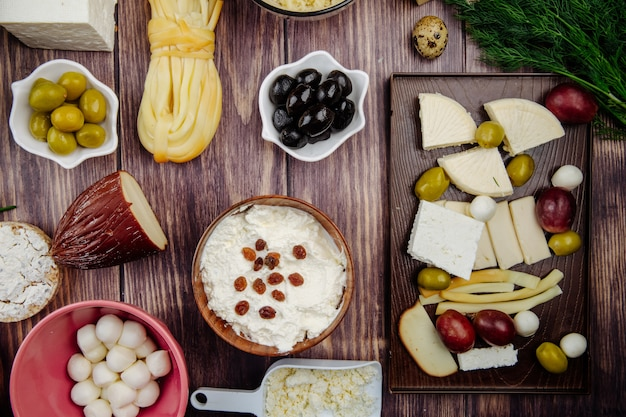 Top view of various types of cheese with pickled olives quail eggs and dill on rustic wood