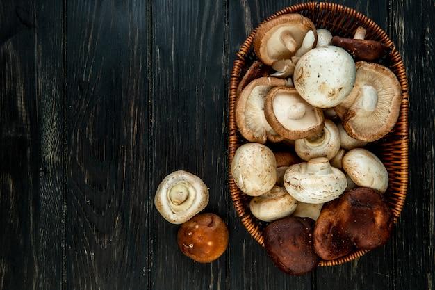 Vista dall'alto di vari tipi di funghi freschi in un cestino di vimini su legno rustico scuro con spazio di copia