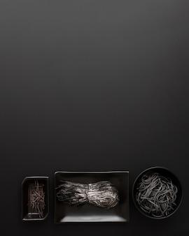 Вид сверху различных видов макарон чернил кальмара в мисках