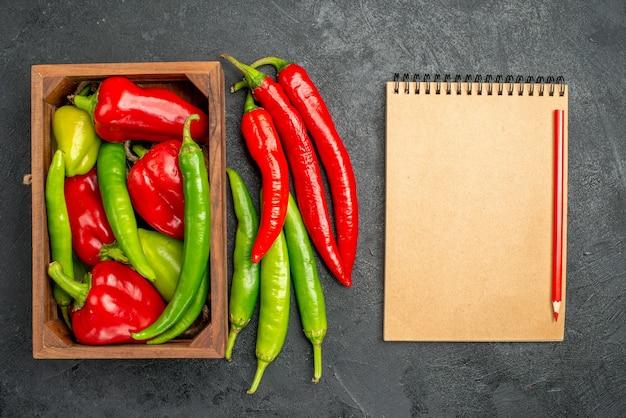 Vista dall'alto vari tipi di peperoni all'interno della scatola vicino al taccuino e alla penna rossa su superficie nera con spazio libero