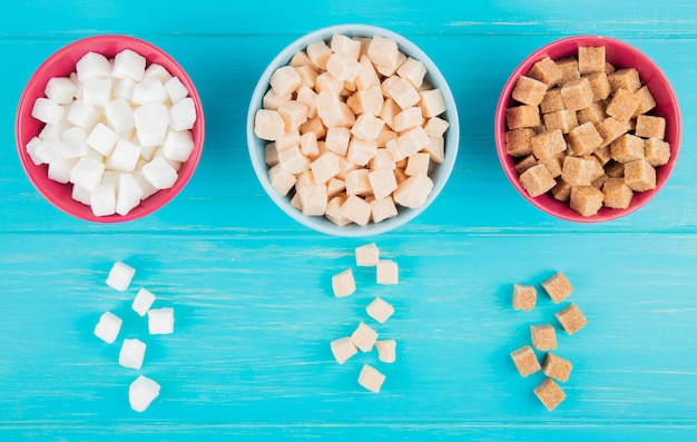 Top view of various types of sugar cubes in bowls on blue wooden background