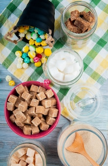 Top view of various types of sugar in glass jars and colorful sugar candies scattered from a bucket on plaid table napkin on rustic background