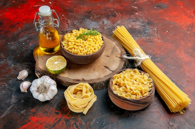 Top view of various types of uncooked pastas and garlic lemon oil bottle on mixed color background