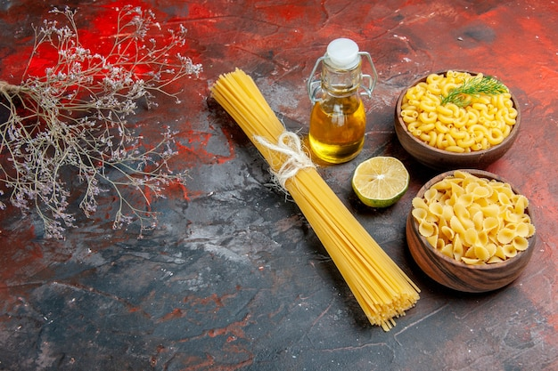 Top view of various types of uncooked pastas and lemon oil bottle on mixed color background