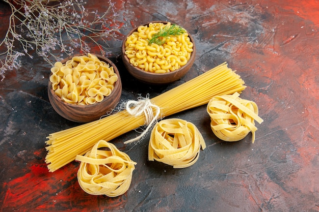 Top view of various types of uncooked pastas on mixed color background
