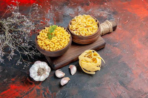 Top view of various types of uncooked pastas on wooden cutting board and garlic on mixed color background