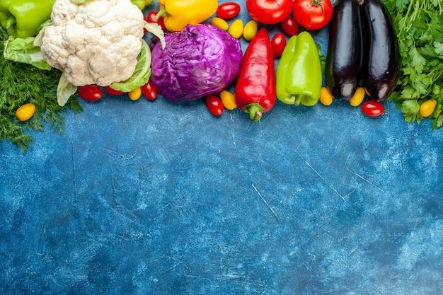 Vista dall'alto varie verdure pomodorini diversi colori peperoni pomodori cumcuat melanzane cavolfiori cavolo rosso in cima al tavolo blu copia posto