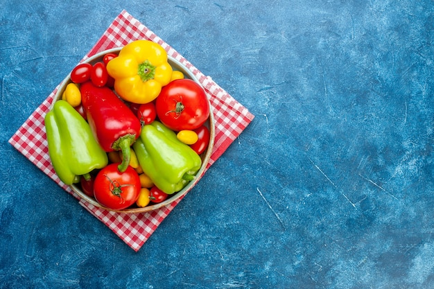 Top view various vegetables cherry tomatoes different colors bell peppers tomatoes cumcuat on platter on red white checkered kitchen towel on blue table copy place