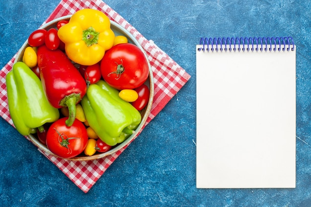 Top view various vegetables cherry tomatoes different colors bell peppers tomatoes cumcuat on platter on red white checkered kitchen towel notepad on blue table