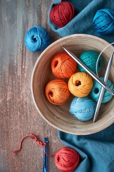 Top view of various yarn balls and latch hook on grey texture