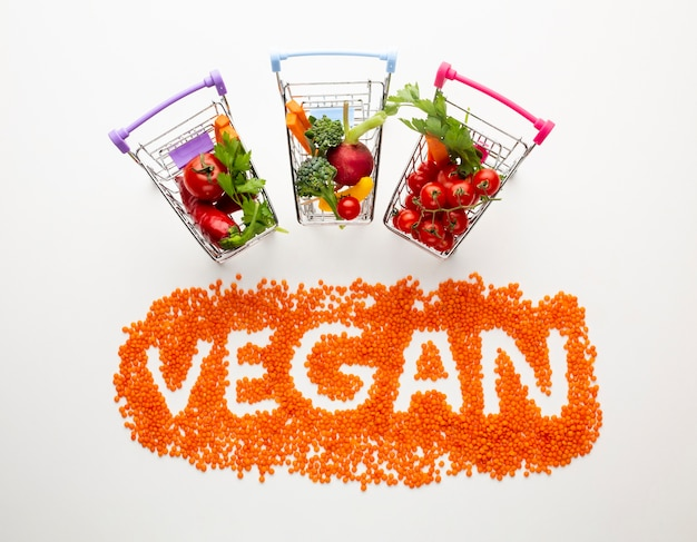 Top view vegan lettering with delicious vegetables in small shopping carts