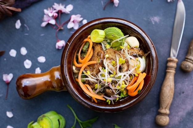 Vista dall'alto di un pasto vegano con funghi, cipolle, carote e porri