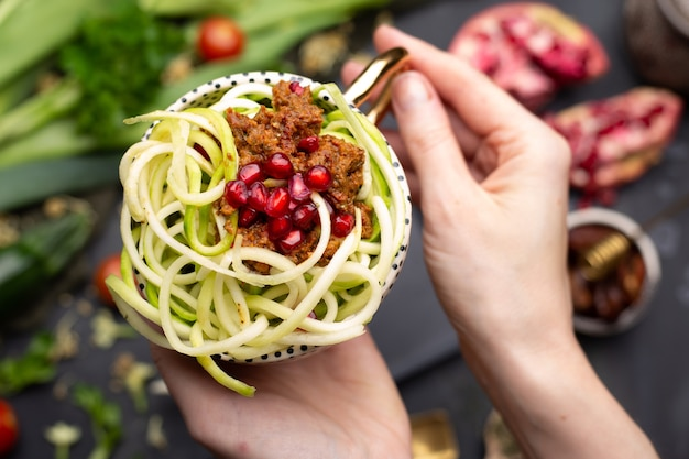Vista dall'alto di un pasto vegano con zucchine a spirale, salsa di pomodoro e melograni nella tazza