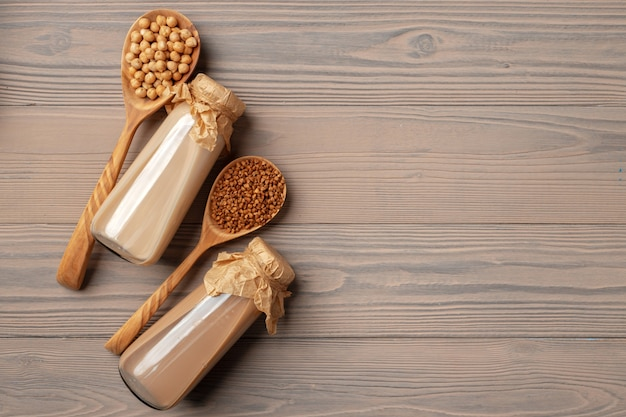 Top view of vegan milk and grains in wooden spoons on wooden surface