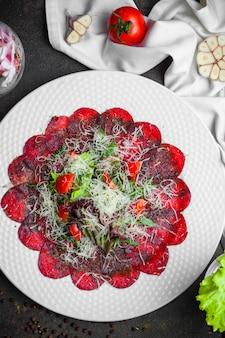 Вид сверху веганский салат со свеклой, чесноком и помидорами