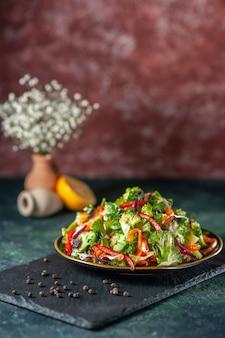 Vista dall'alto di insalata vegana con ingredienti freschi in un piatto e pepe su tagliere nero