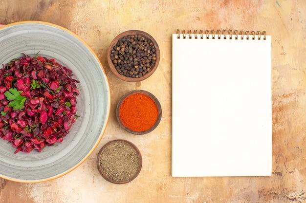 上面図緑の葉のビーガンサラダは、右側にテキスト用の空白がある木製のテーブルで、黒胡椒で挽いた黒胡椒とターメリックを混ぜ合わせます