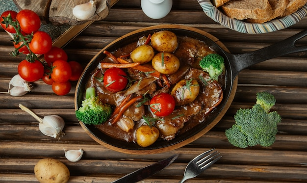 Top view vegetable beef stew in a pottery pan.