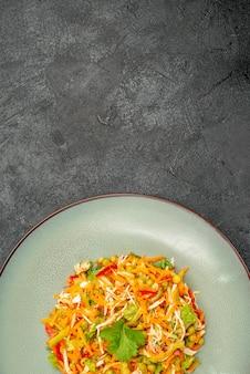 Insalata di pollo vegetale vista dall'alto all'interno del piatto su cibo dietetico per insalata di salute da scrivania scura