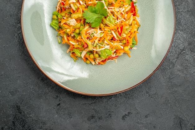Insalata di pollo vegetale vista dall'alto all'interno del piatto sul cibo dietetico per insalata di salute del pavimento scuro