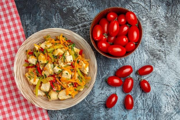 Вид сверху овощной куриный салат с помидорами на светлом столе