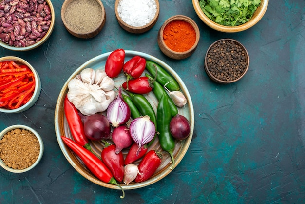 Вид сверху овощной состав лук чеснок перец приправы на темно-синем фоне пищевой ингредиент еды цвет продукта