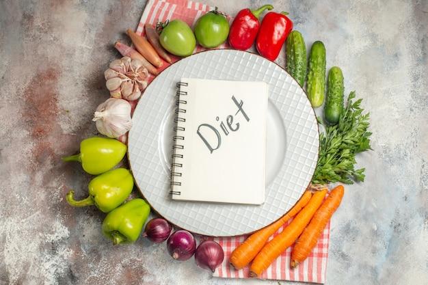 上面図野菜組成ピーマンにんじんにんにくと他の野菜を白い机の上に