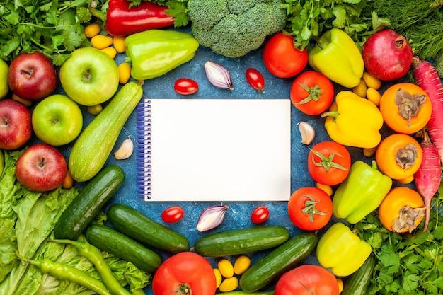 Vista dall'alto composizione vegetale con frutta fresca su scrivania blu colore insalata di dieta matura pasto di vita sana