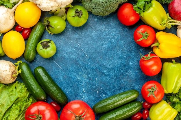 Vista dall'alto composizione vegetale con frutta fresca sul pavimento blu dieta insalata vita sana colore maturo